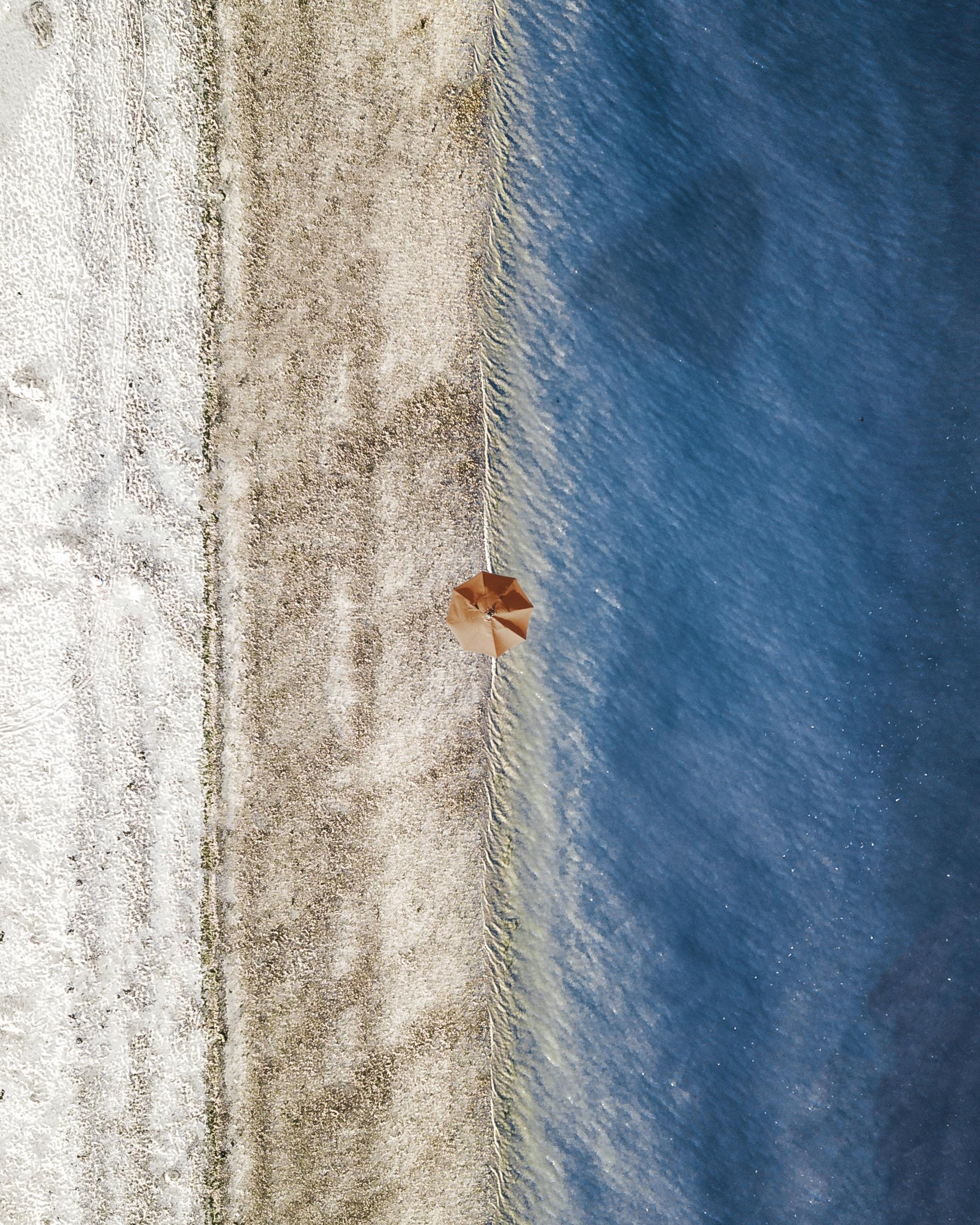 aerial photograph of orange umbrella near body of water