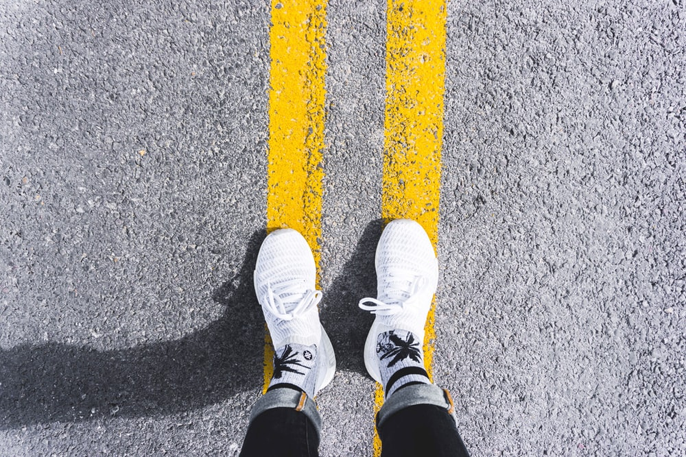 person standing on gray asphalt road with yellow paint