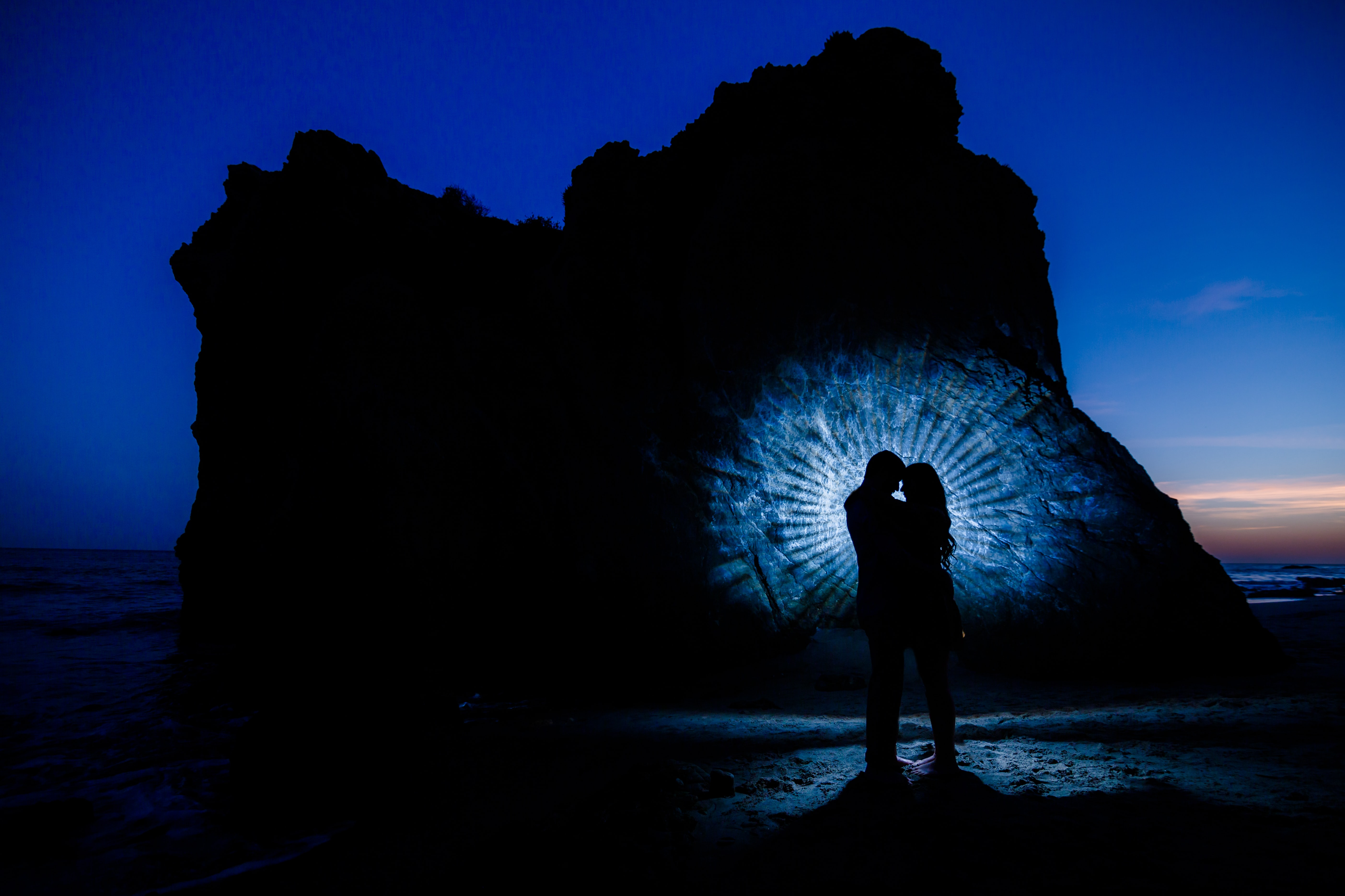 silhouette of couple near rock formation during night time