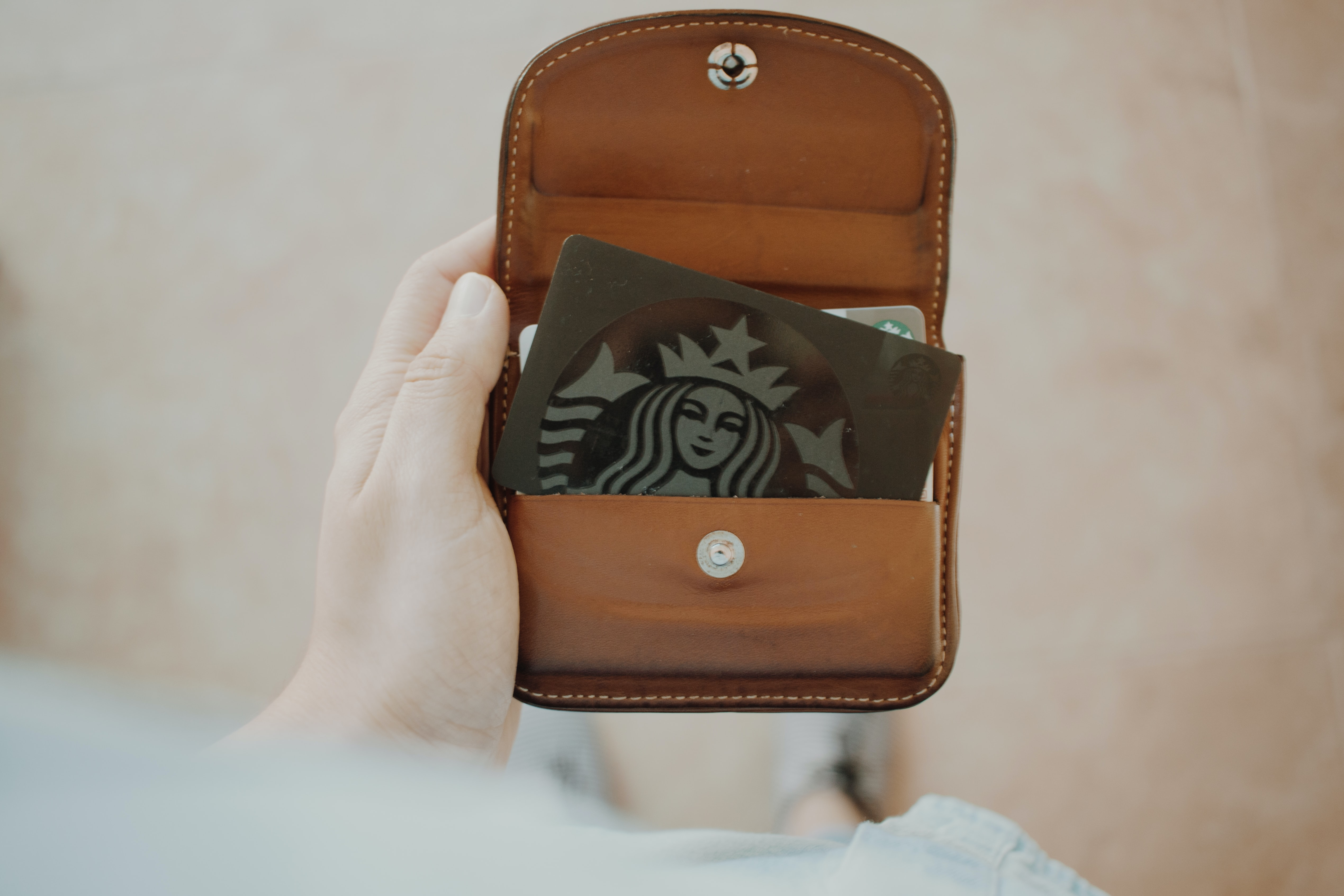 green Starbucks gift card inside brown leather wallet