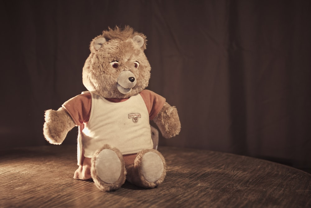 brown bear plush toy placed on brown wooden surface