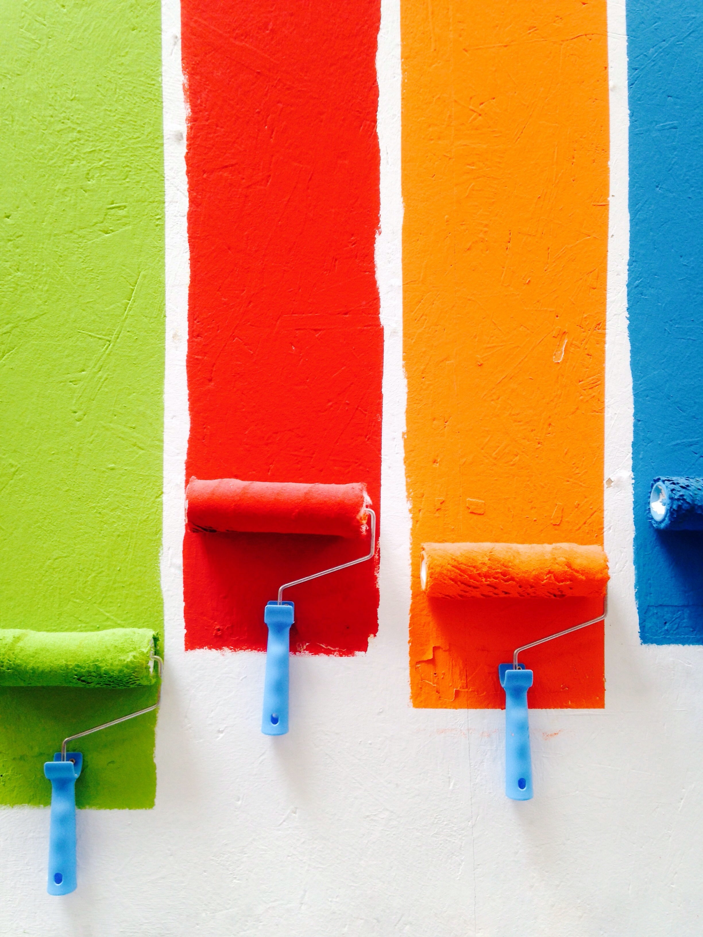 four orange, green, blue, and red paint rollers