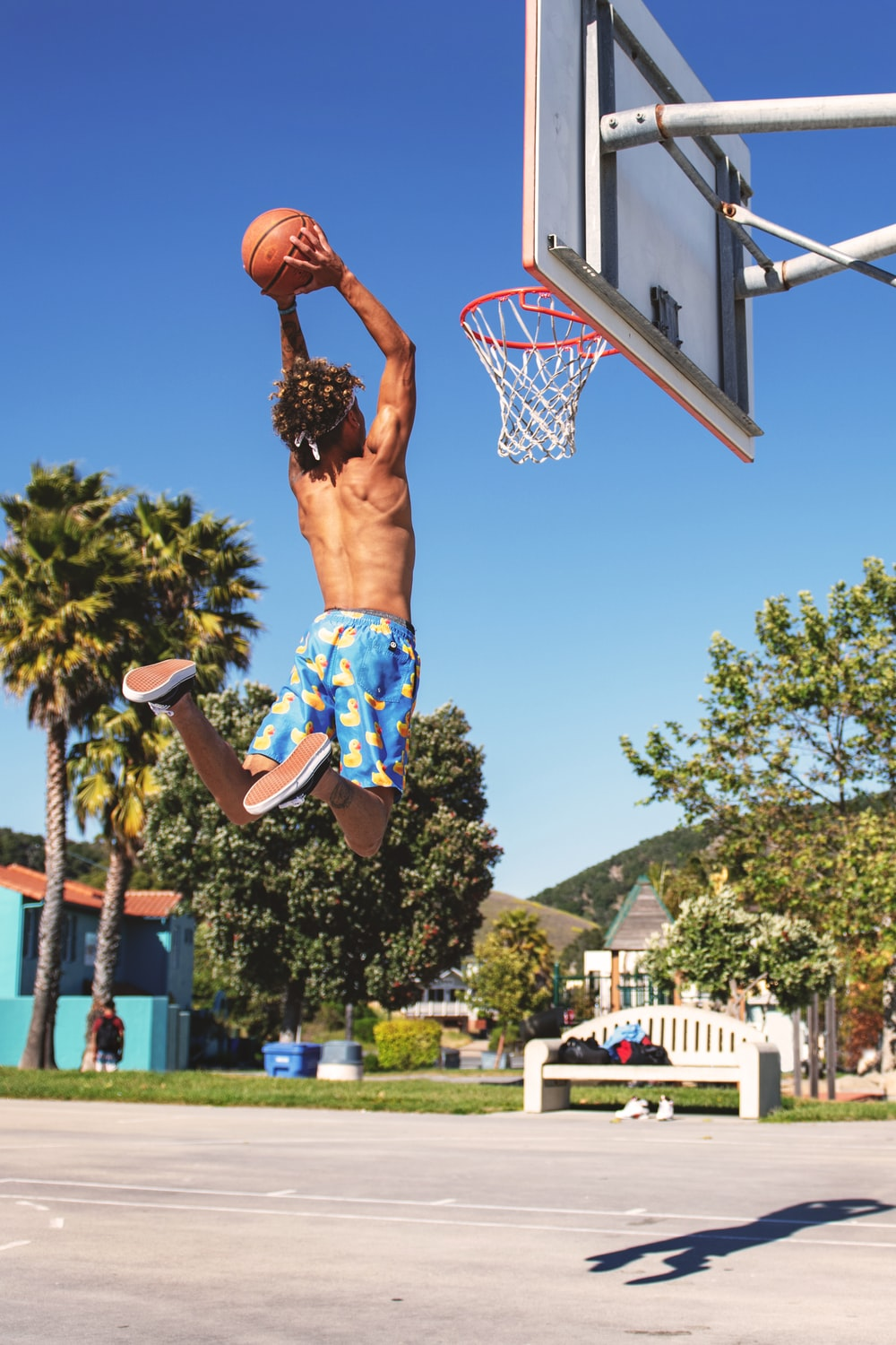 person dunking ball under blue sky during daytime