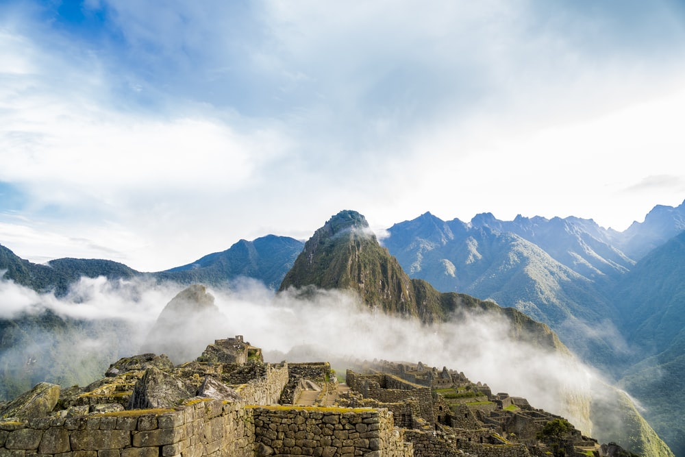 photo of ruins beside wall covering fogs