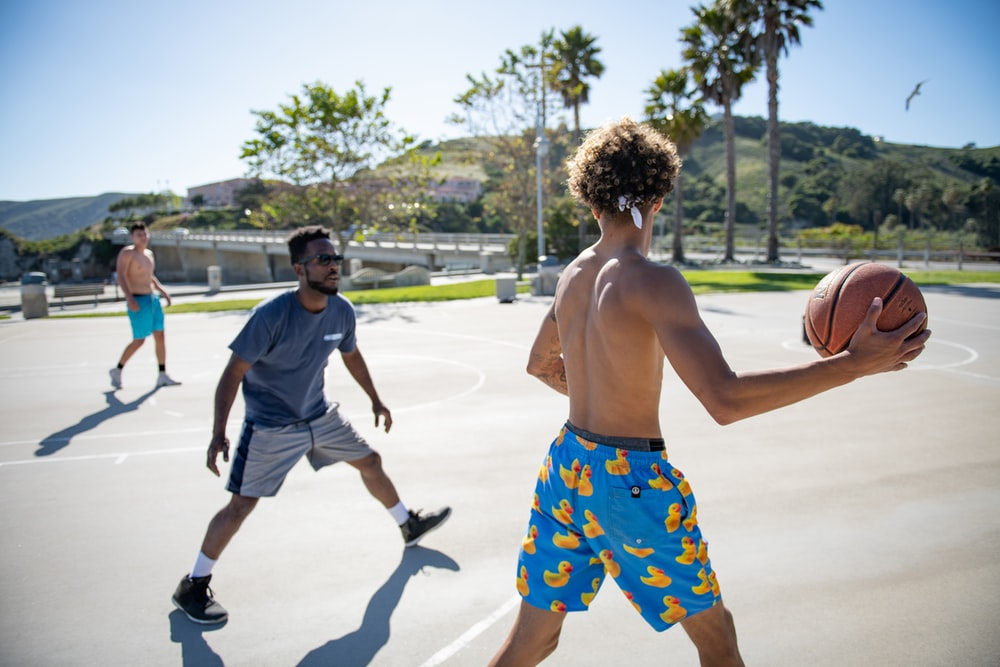 three men playing basketball
