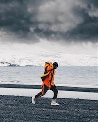 person wearing orange jacket standing near body of water