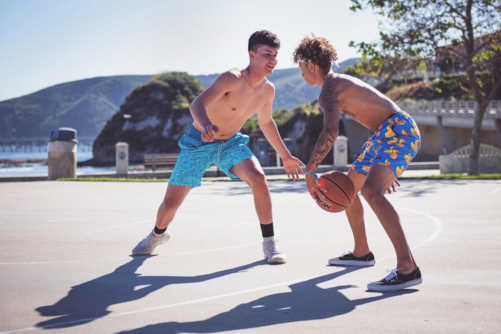 two topless men playing basketball during daytime