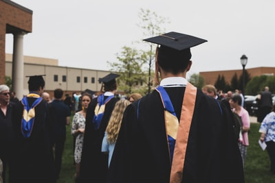 man wearing academic gown graduation teams background