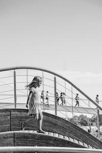 grayscale photo of girl walking on bridge