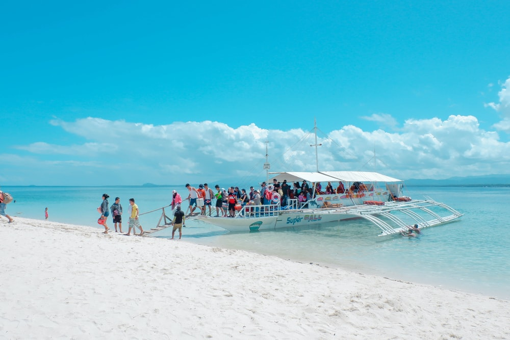 people in white boat on seashore