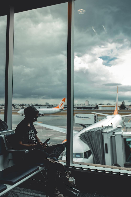 man browsing his phone in airport