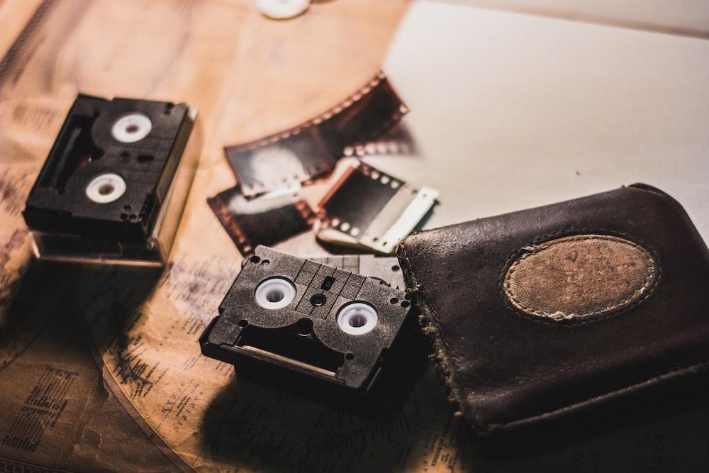 black leather bi-fold wallet beside cassettes