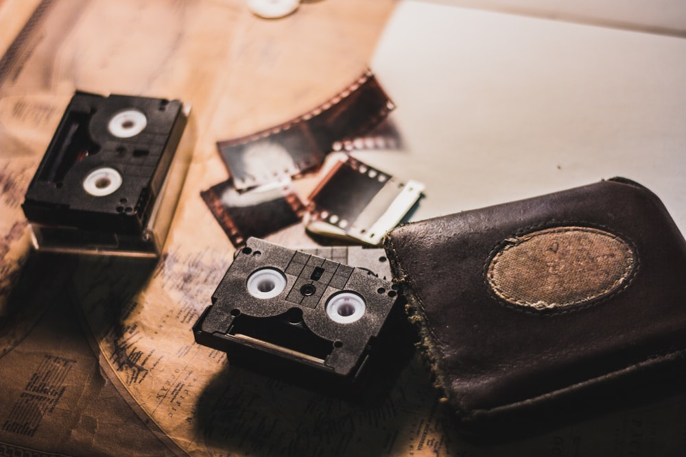 black leather bi-fold wallet beside cassettes