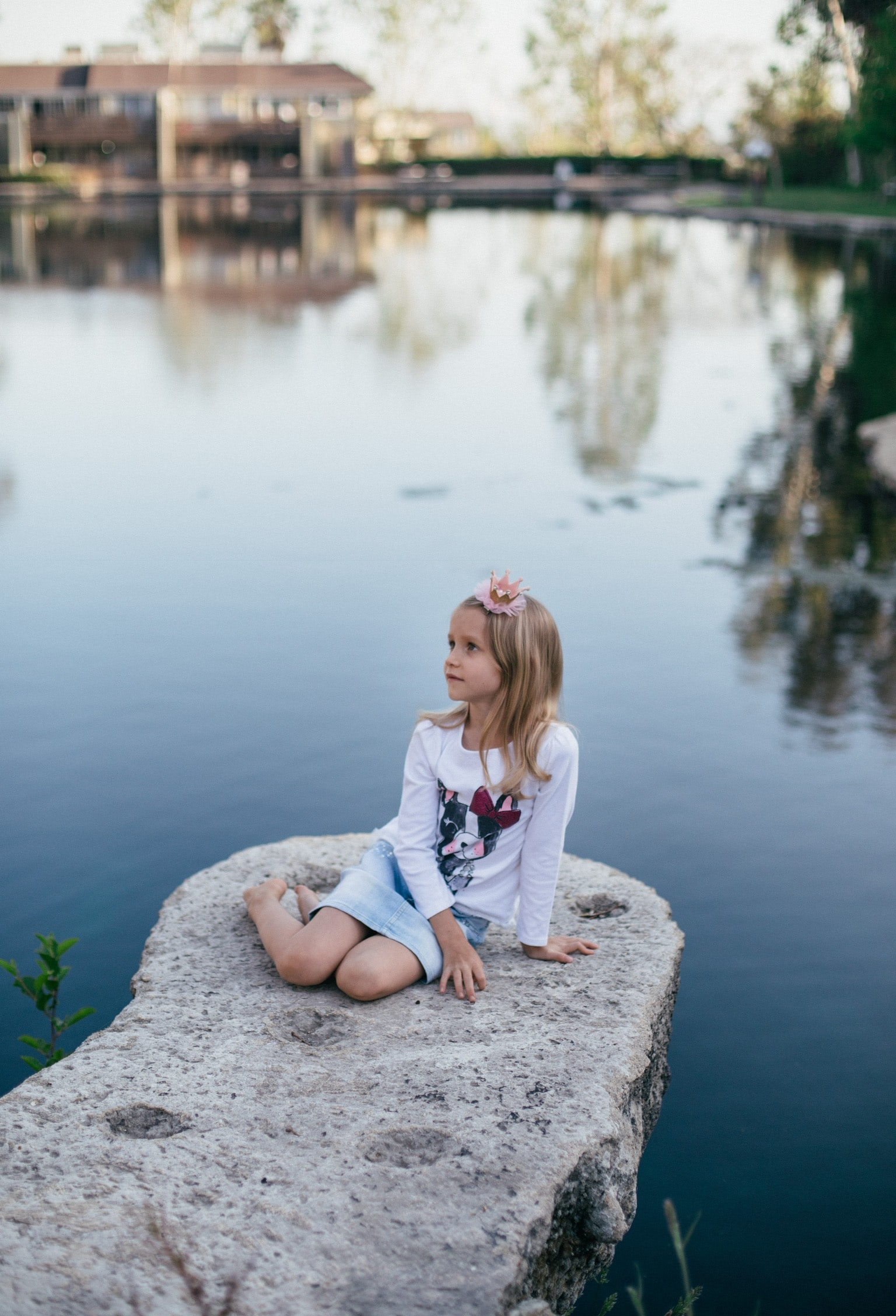 toddler girl sitting on gray stone beside body of water at daytime