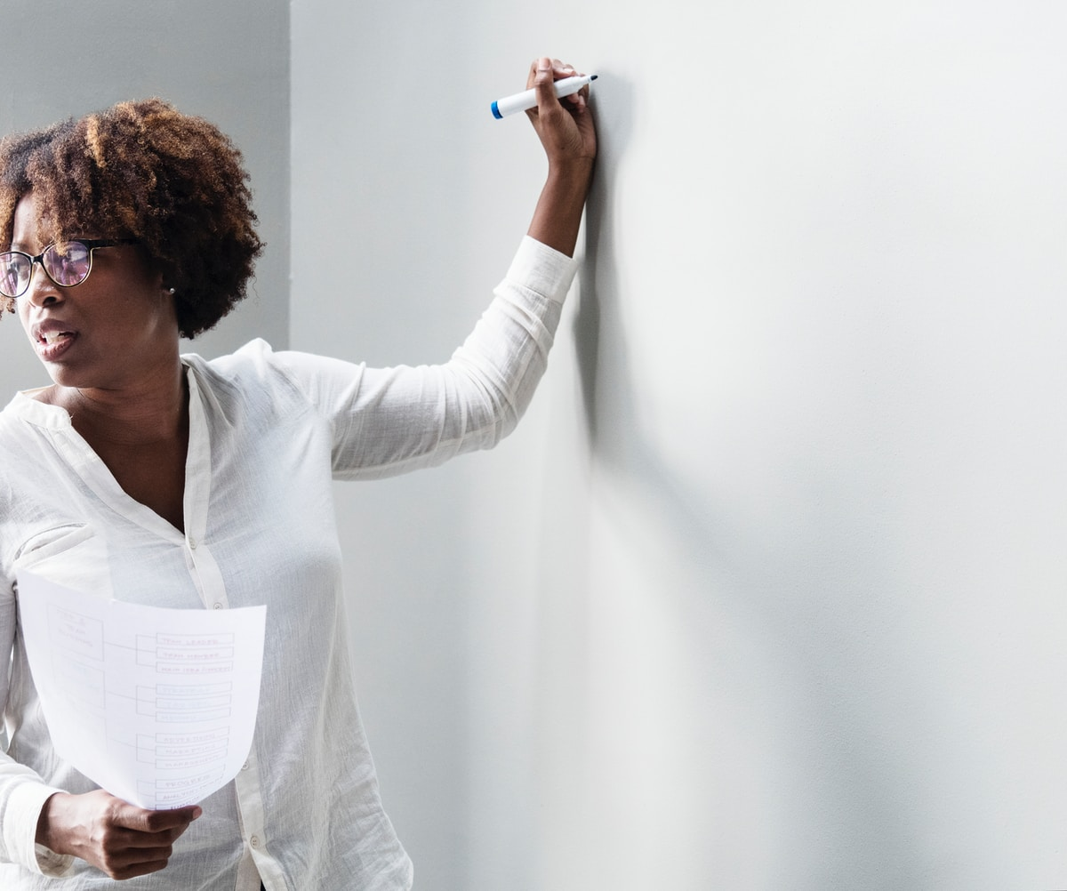 Photograph of a business woman standing in front of a blank whiteboard.