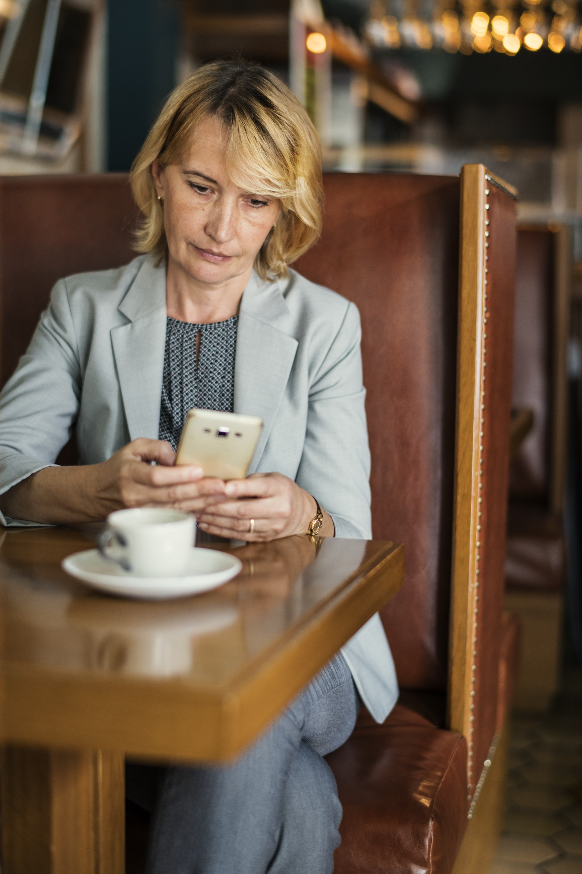 woman using white smartphone on front of table
