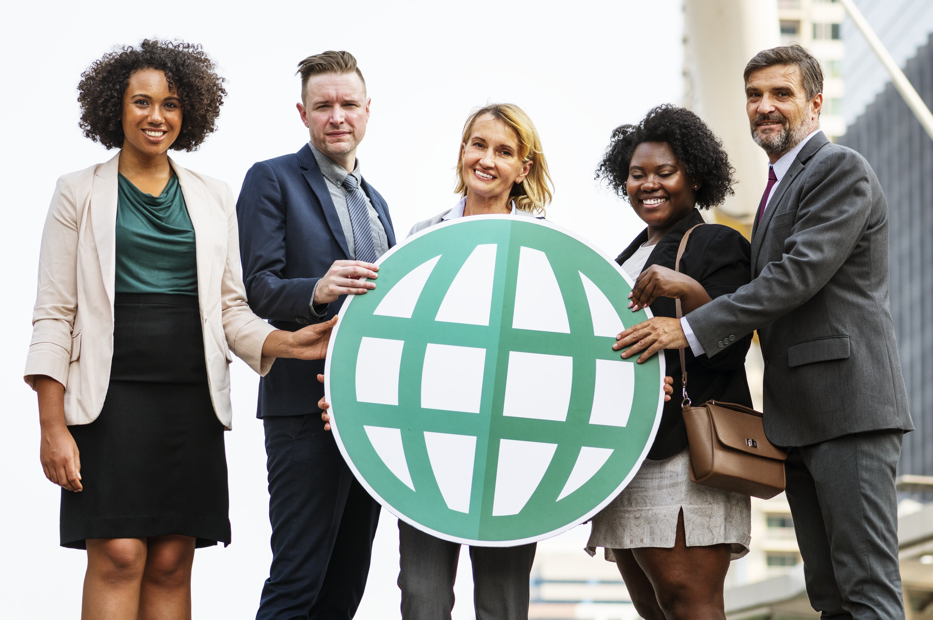 five person holding round white and green globe cutout board