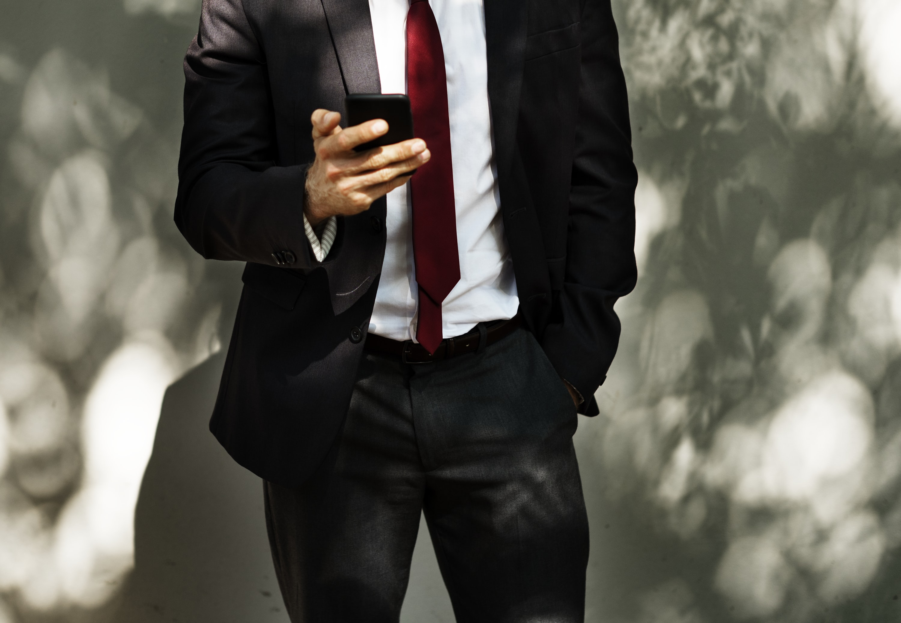 man standing while holding smartphone