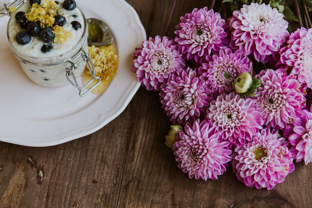 pink daliah flowers beside white plate