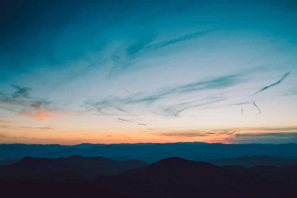 silhouette of mountains under golden hour