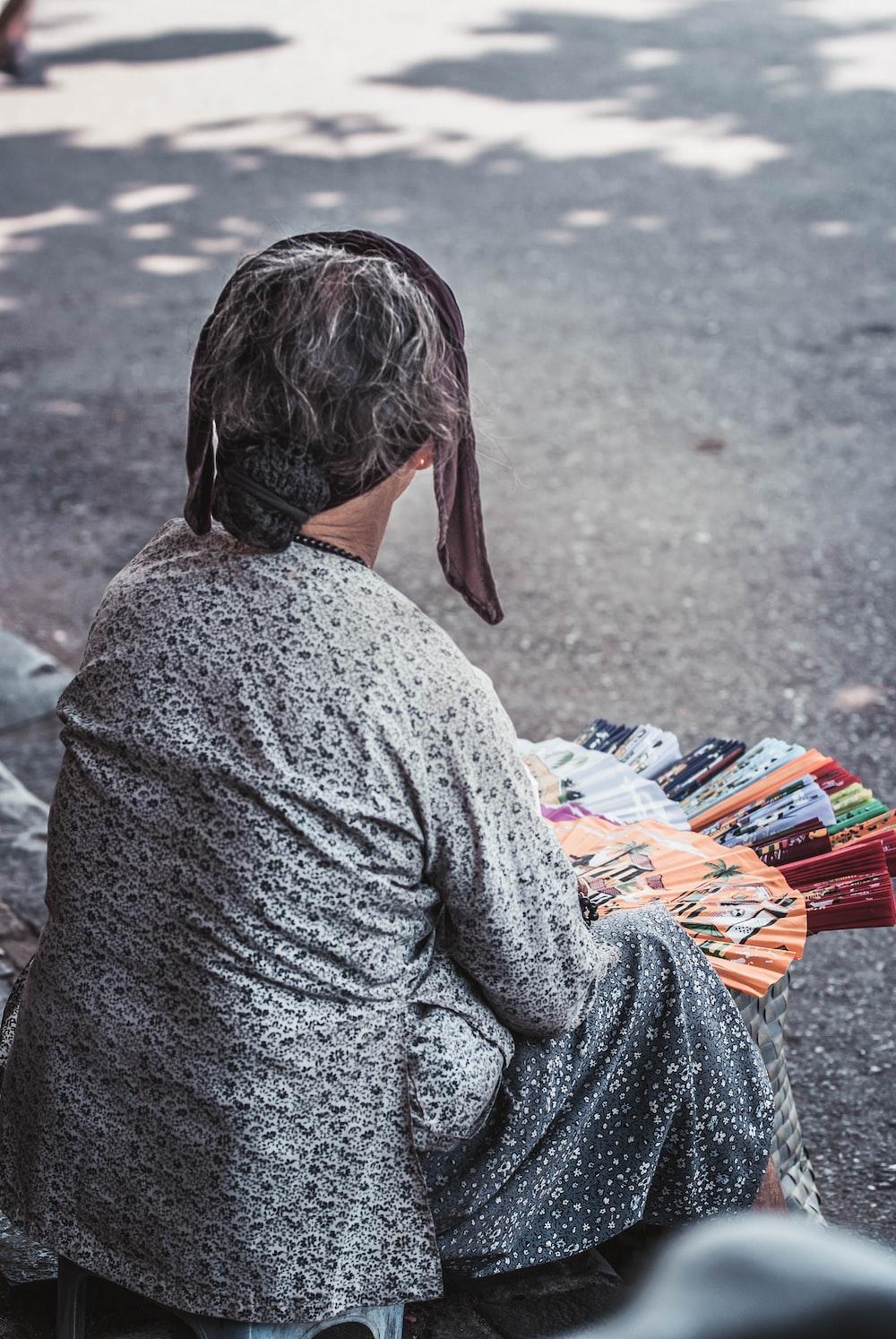 woman sitting beside road