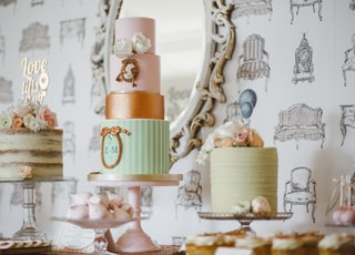 three assorted cakes near white framed mirror