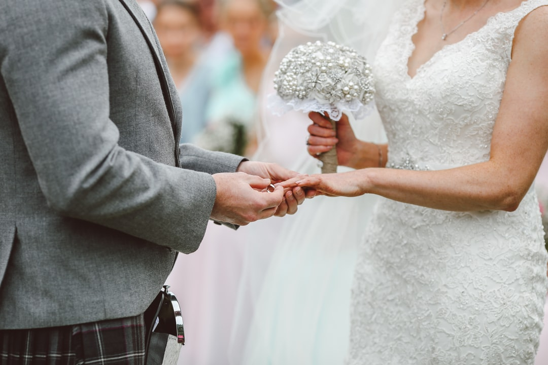 Man places ring on finger during the vows