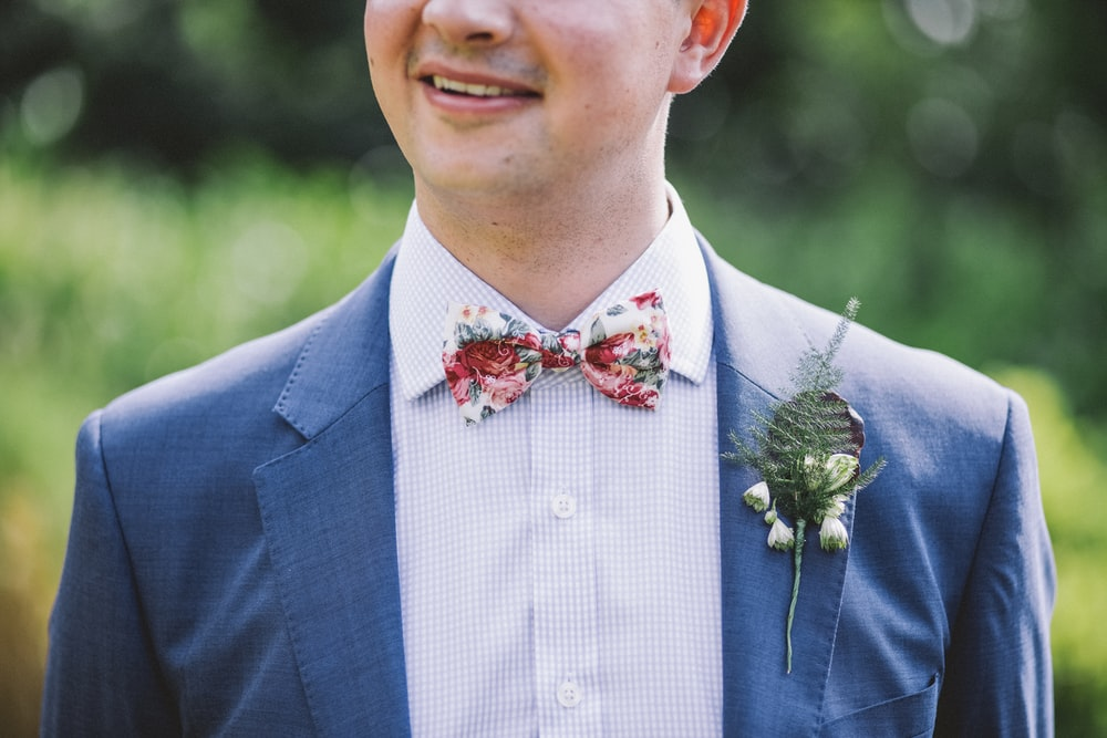 man wearing blue notched-lapel blazer with red and white bowtie at daytime
