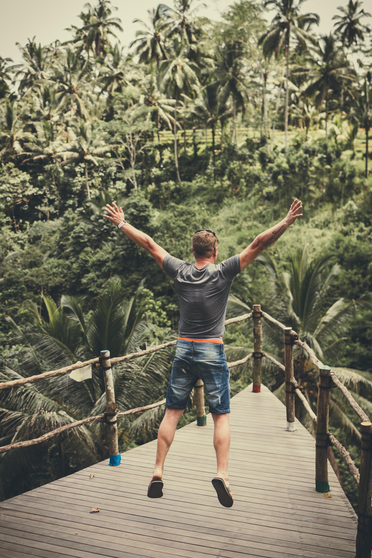 man jumping and raising his arms