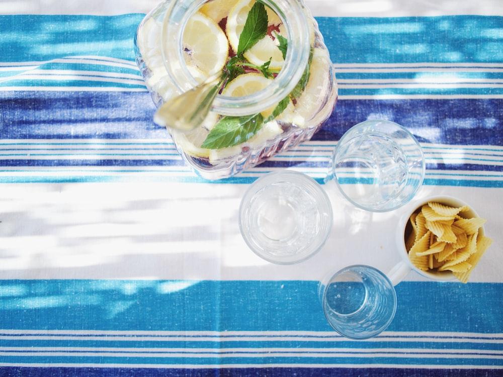 lime juice bottle beside shot glasses on table