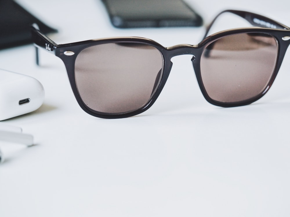 brown sunglasses on white wooden table