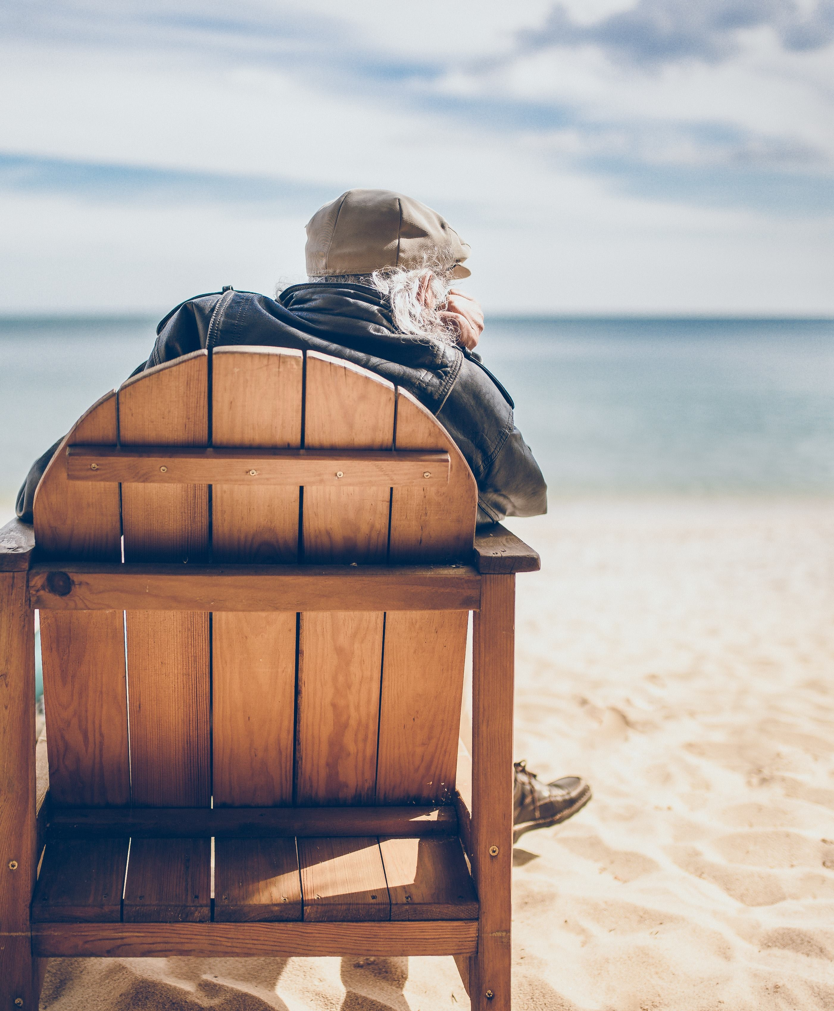 person sitting on brown wooden chair in seashore