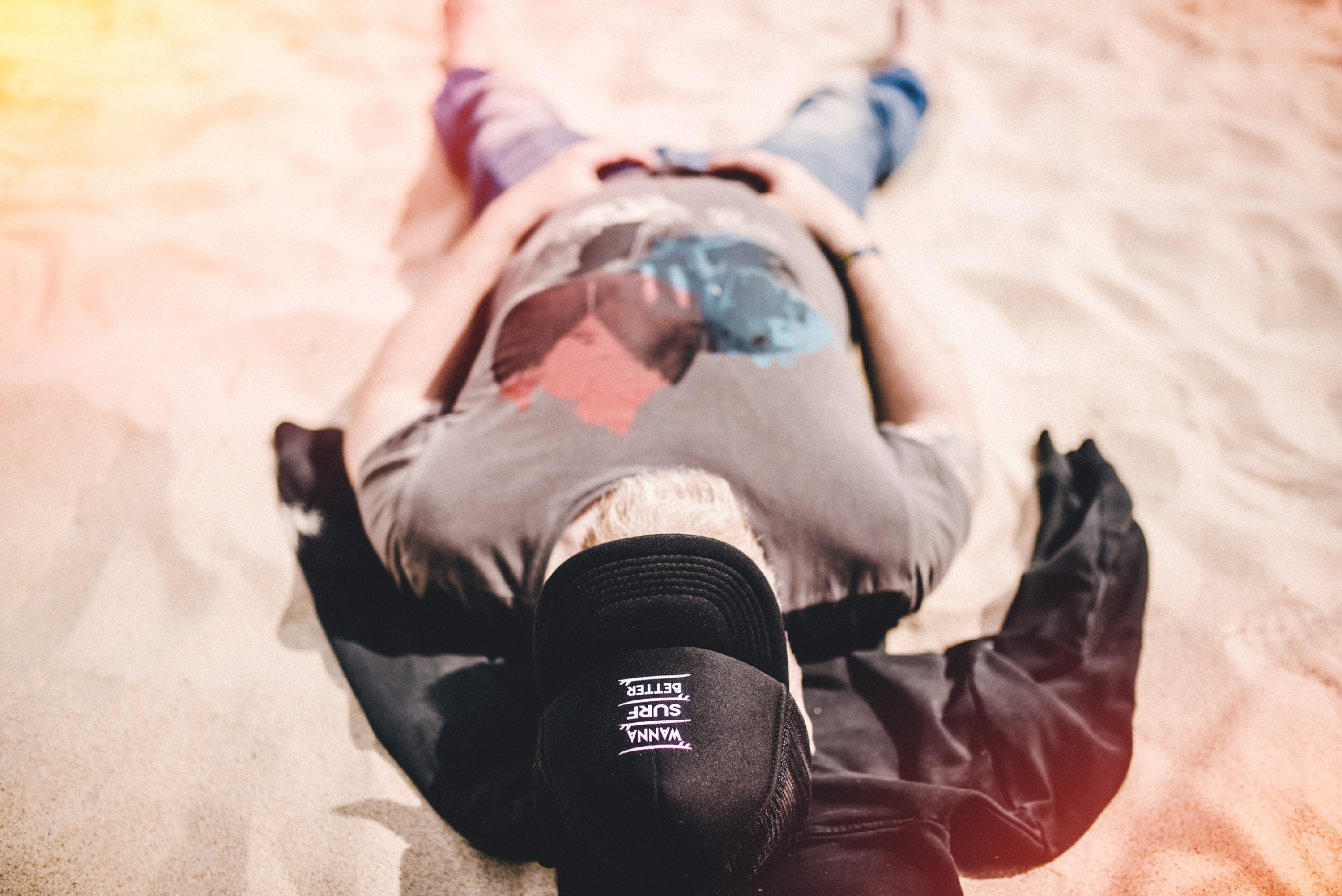 man in gray shirt lying on sand