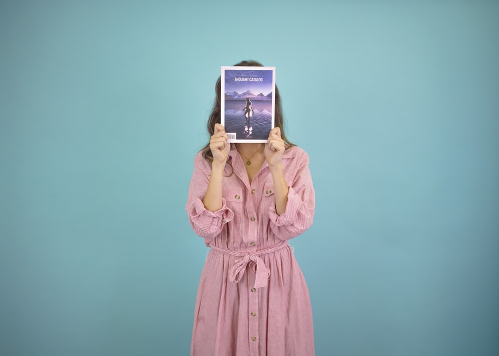 woman wearing pink dress covering her face with book