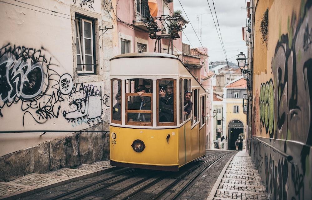 people inside tram between buildings