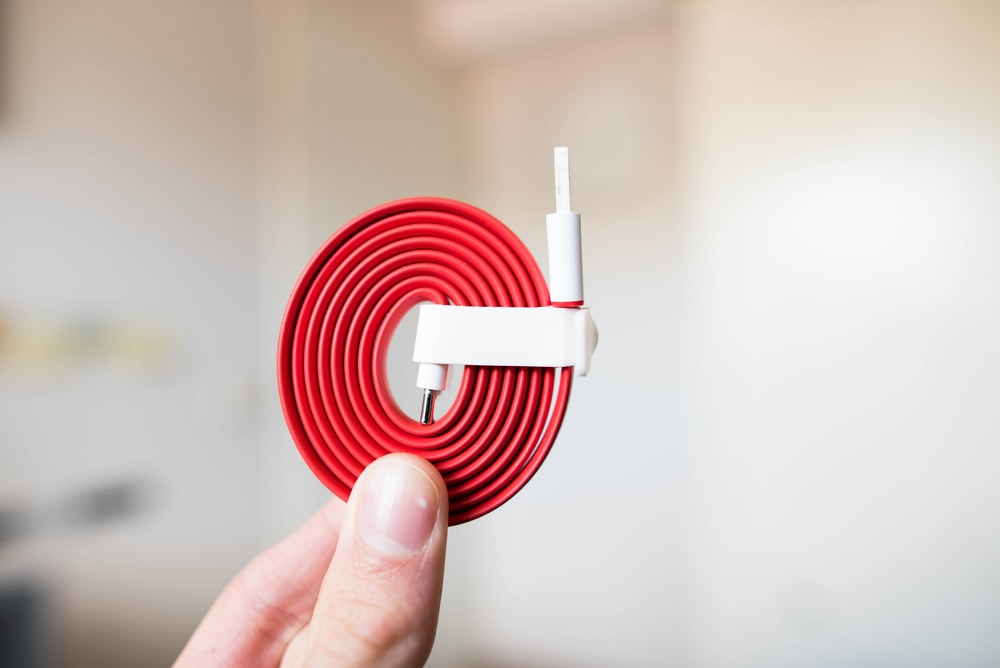 person holding white and red cable