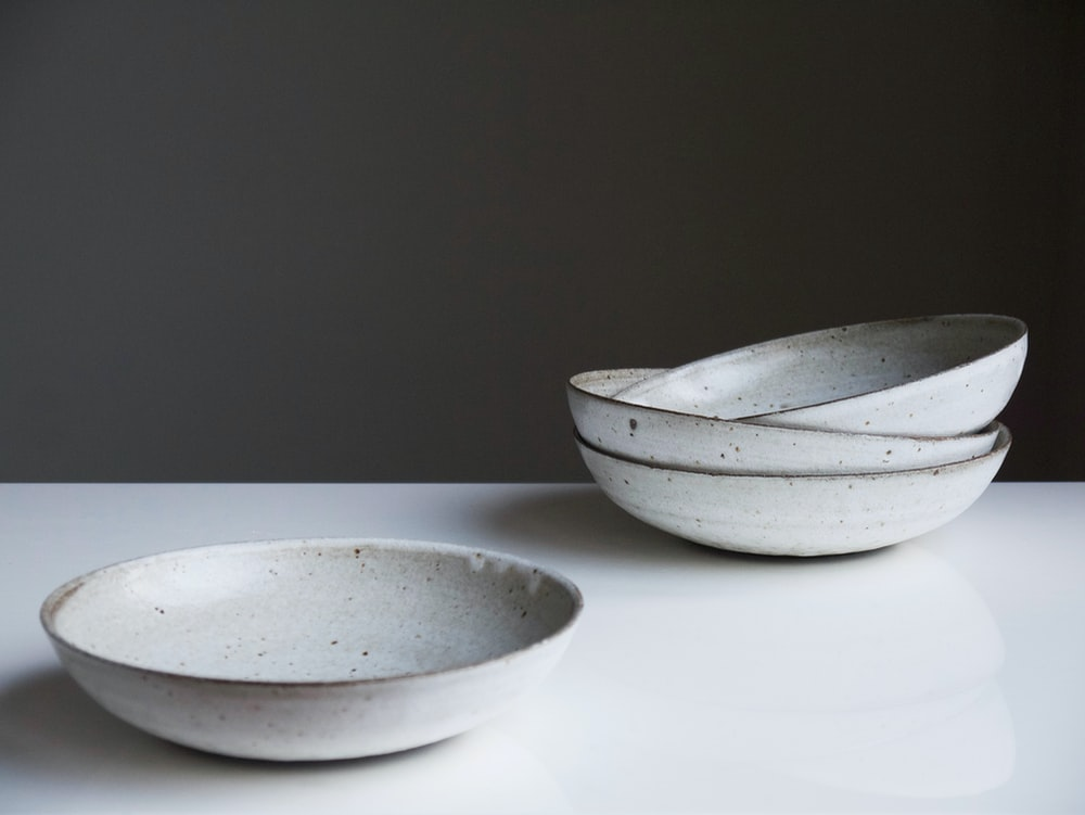 four round white ceramic bowls on white surface