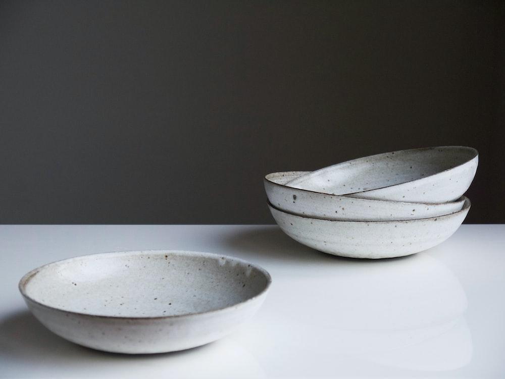 four round white ceramic bowls on white surface