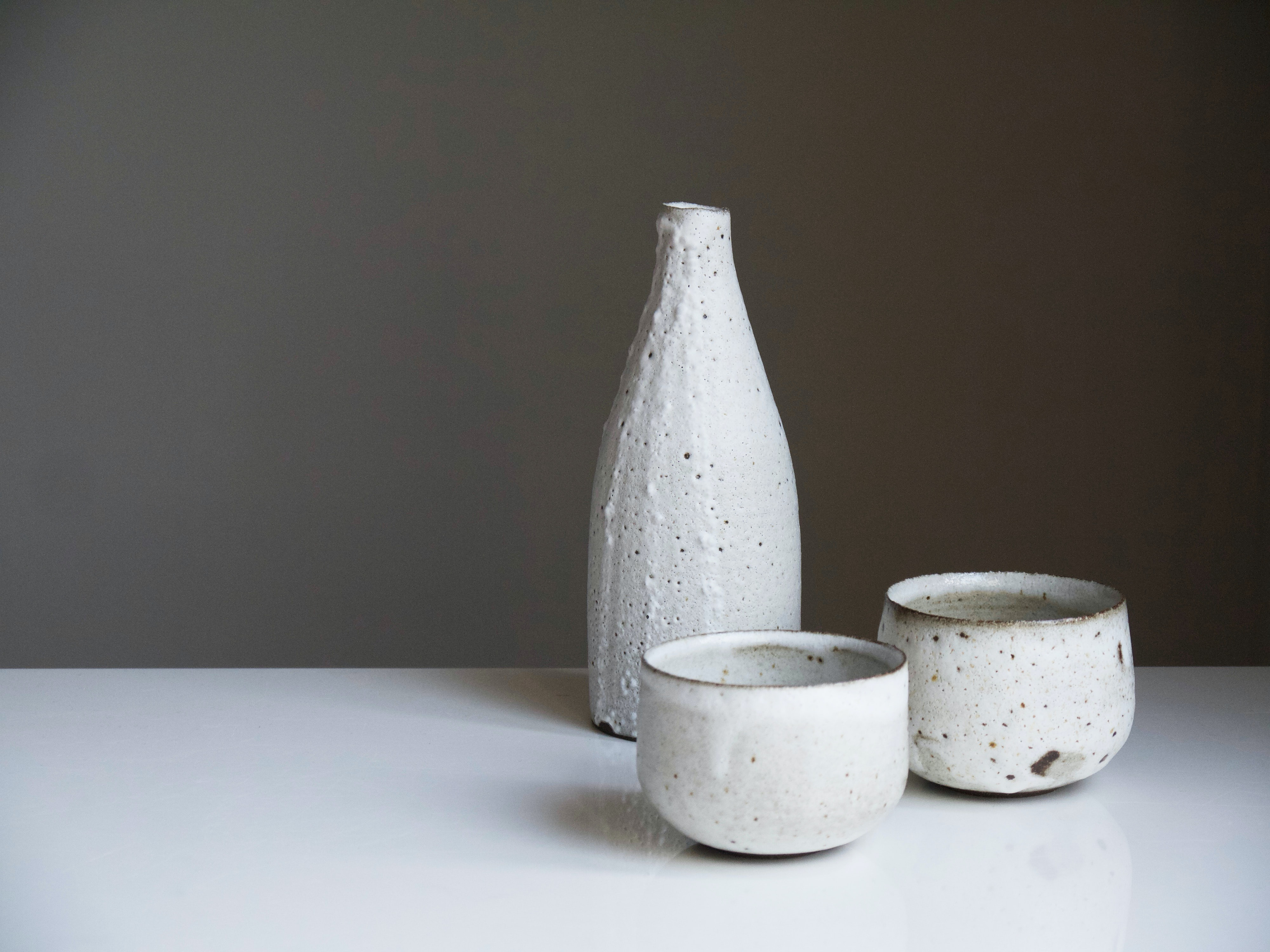 two white ceramic bowls and bottle on white table
