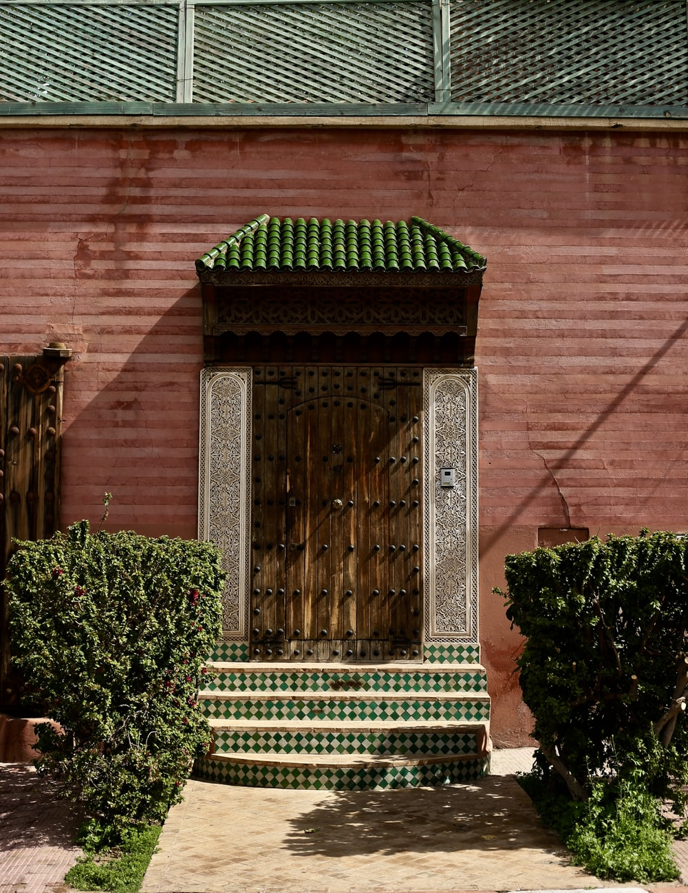 photography of pink concrete house near plants