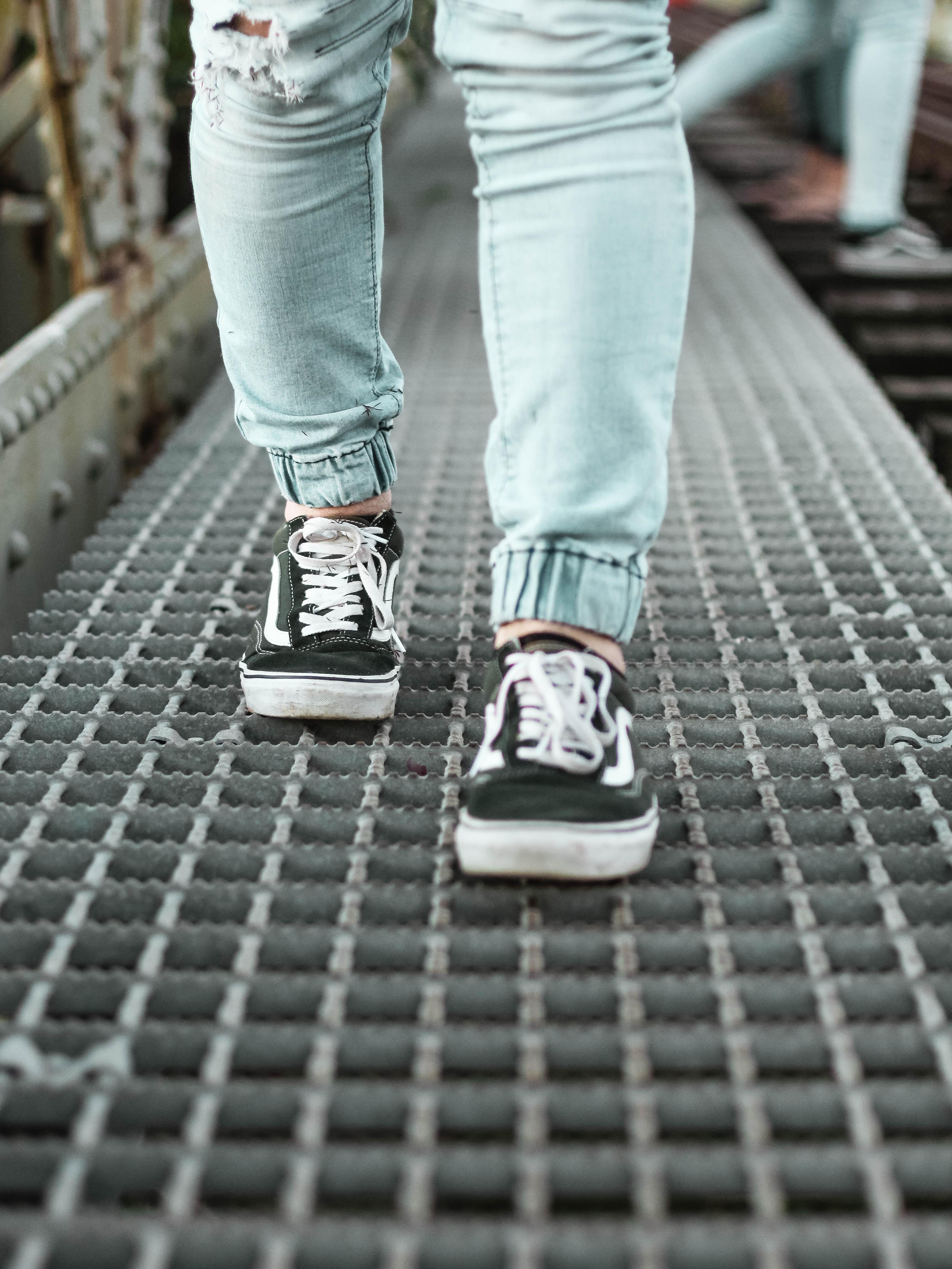 person wearing black Vans Old Skool low-top sneakers