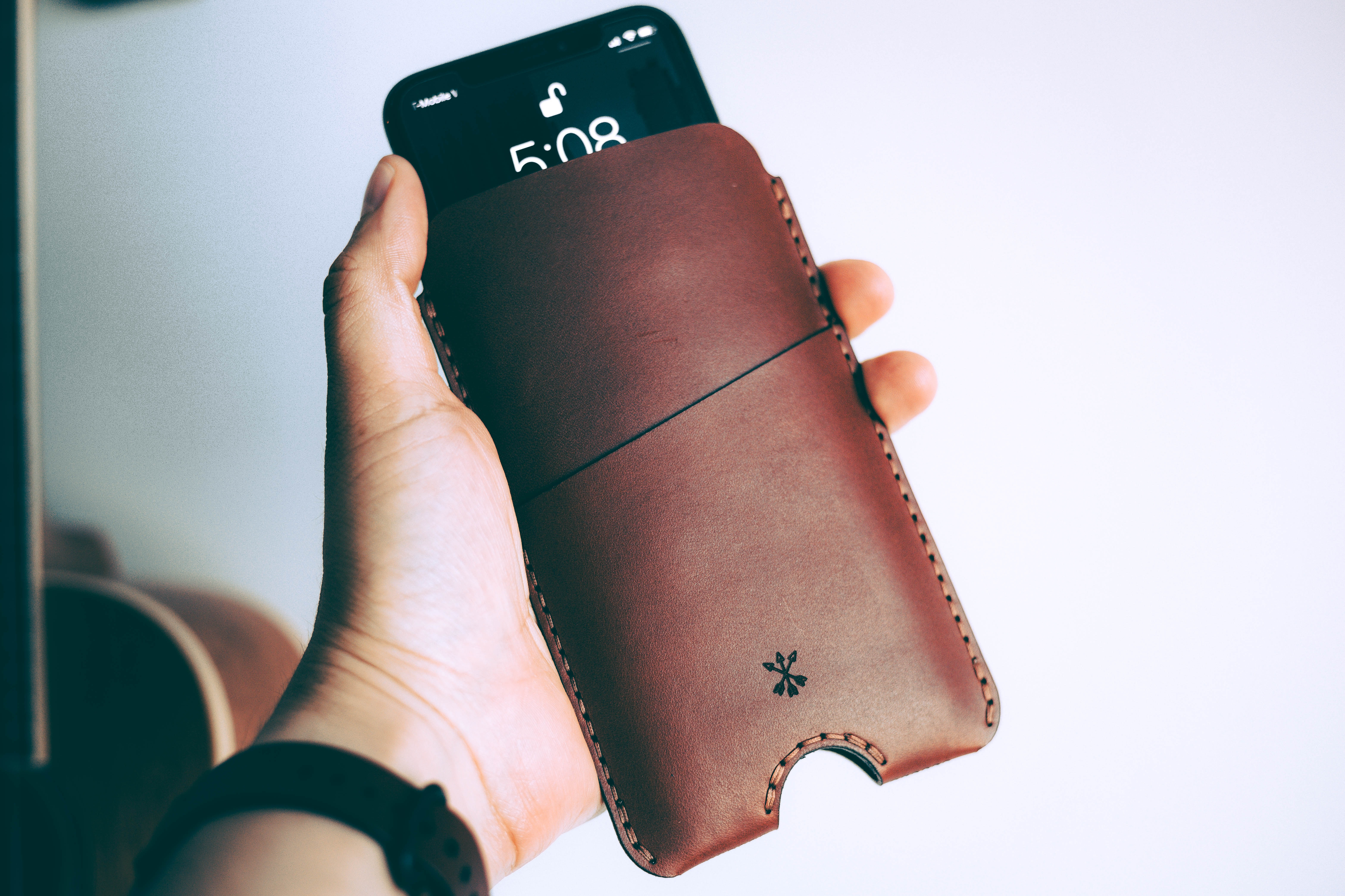 person holding black smartphone with pouch