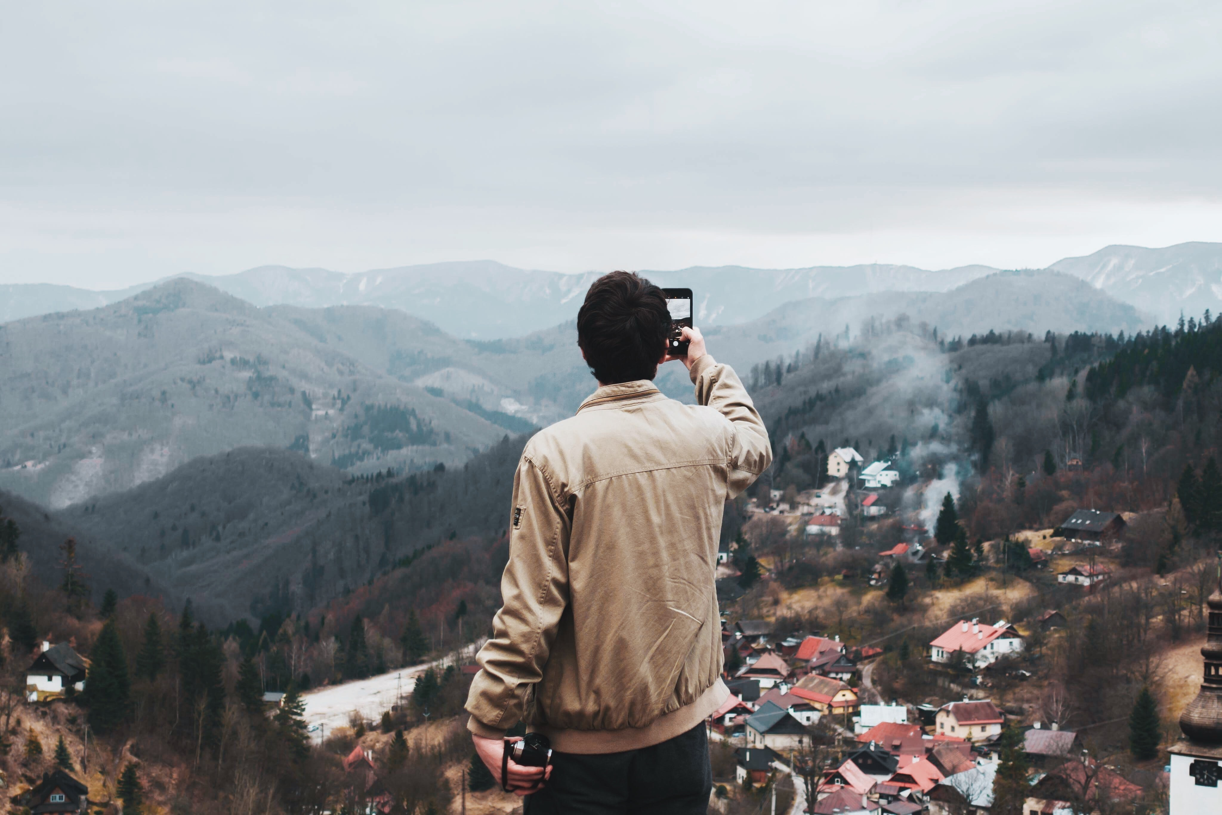man taking a photo of city