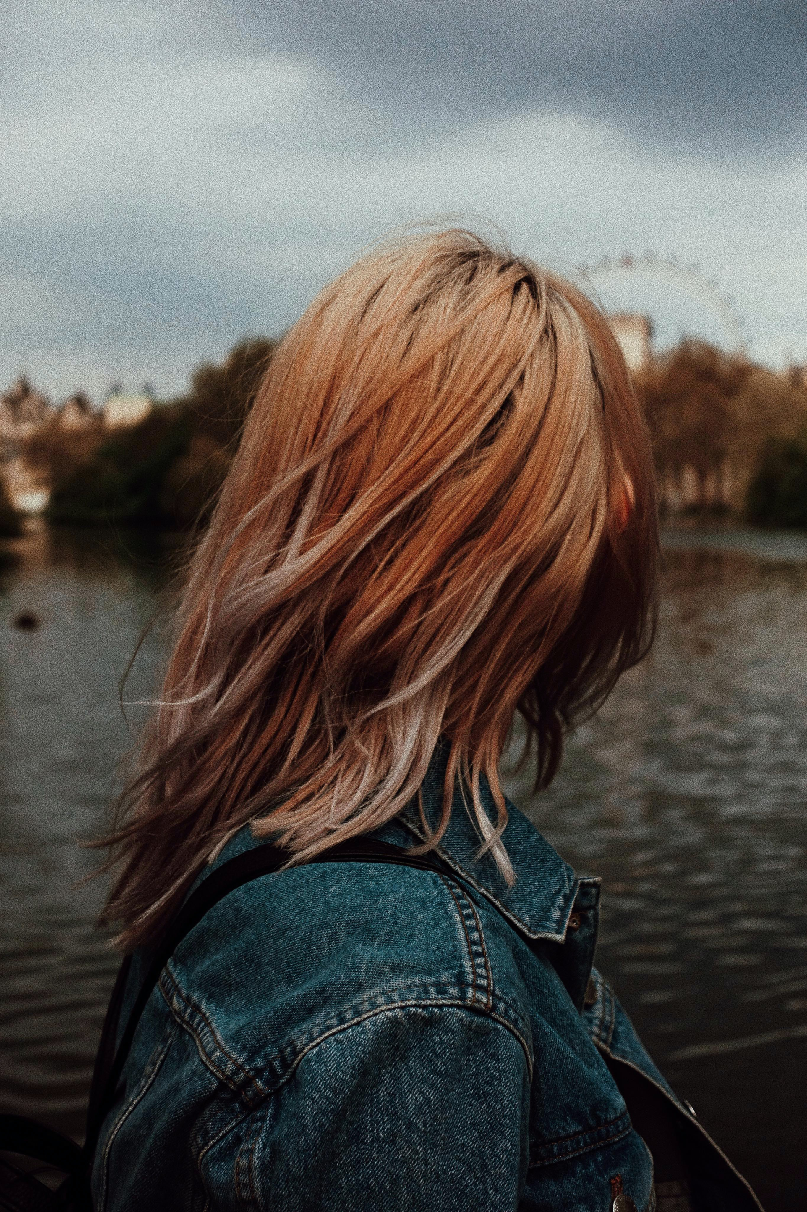 woman in blue denim jacket in front of body of water