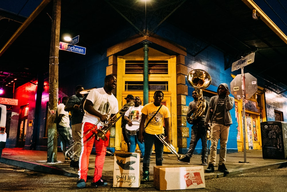 people holding musical instruments while standing on street during nighttime