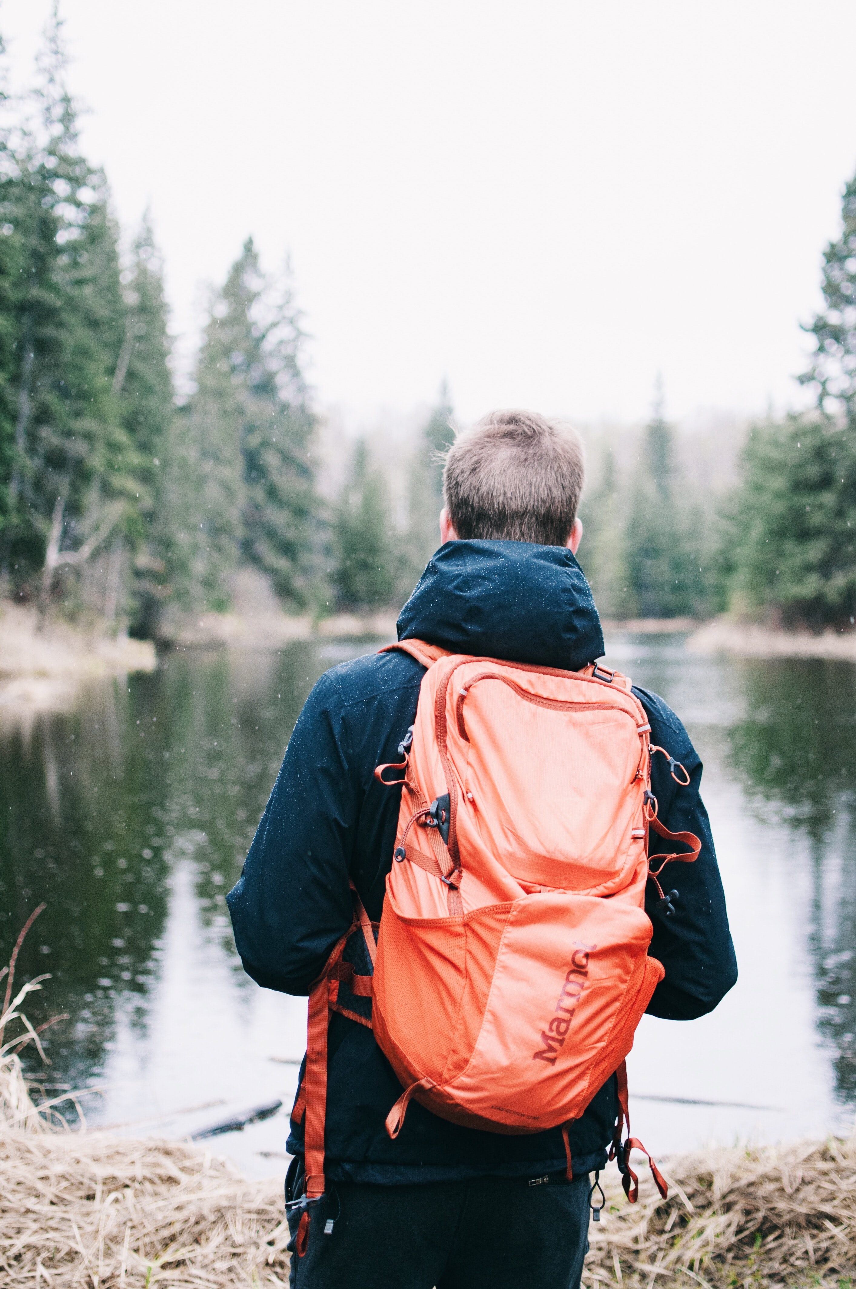 man wearing blue jacket and red backpack facing body of water
