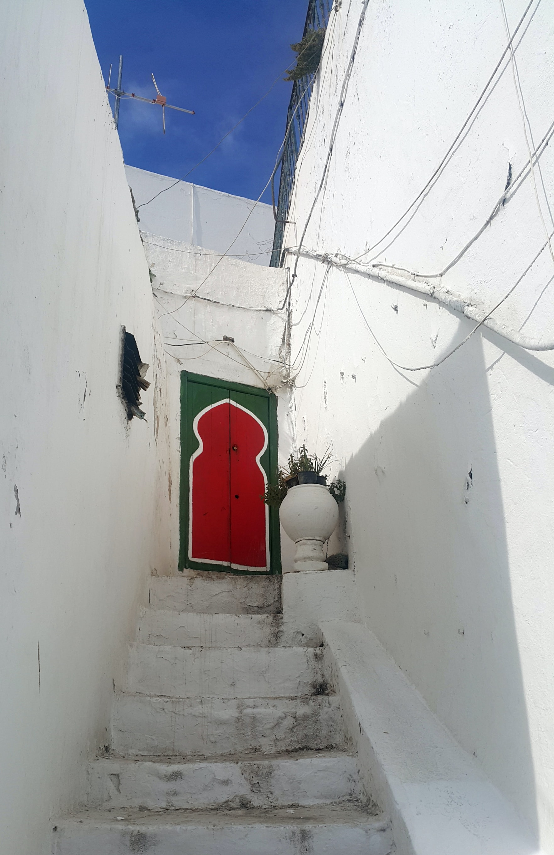 red-and-green door near white wall