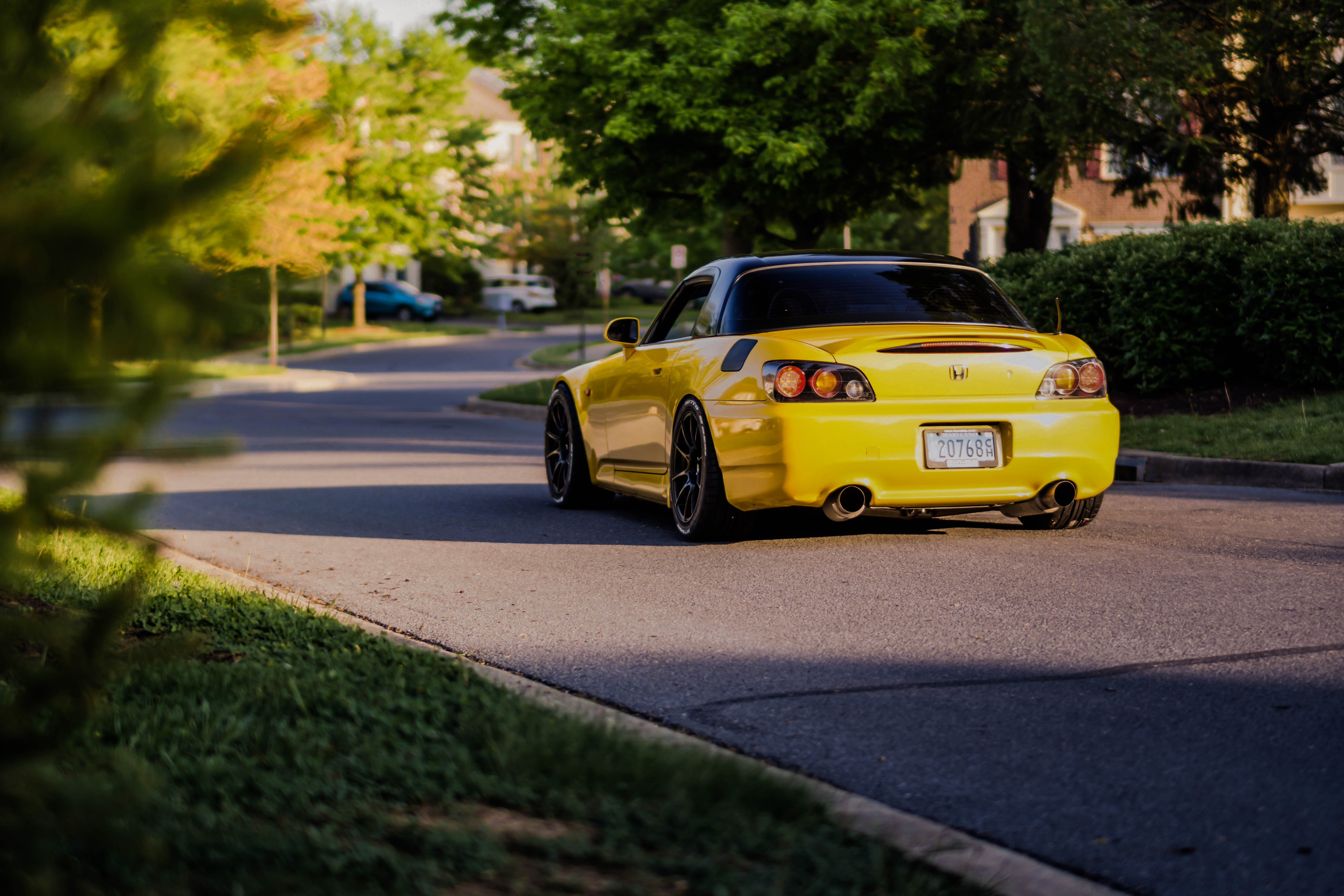 yellow Honda coupe on gray concrete road between green trees and plants during daytime