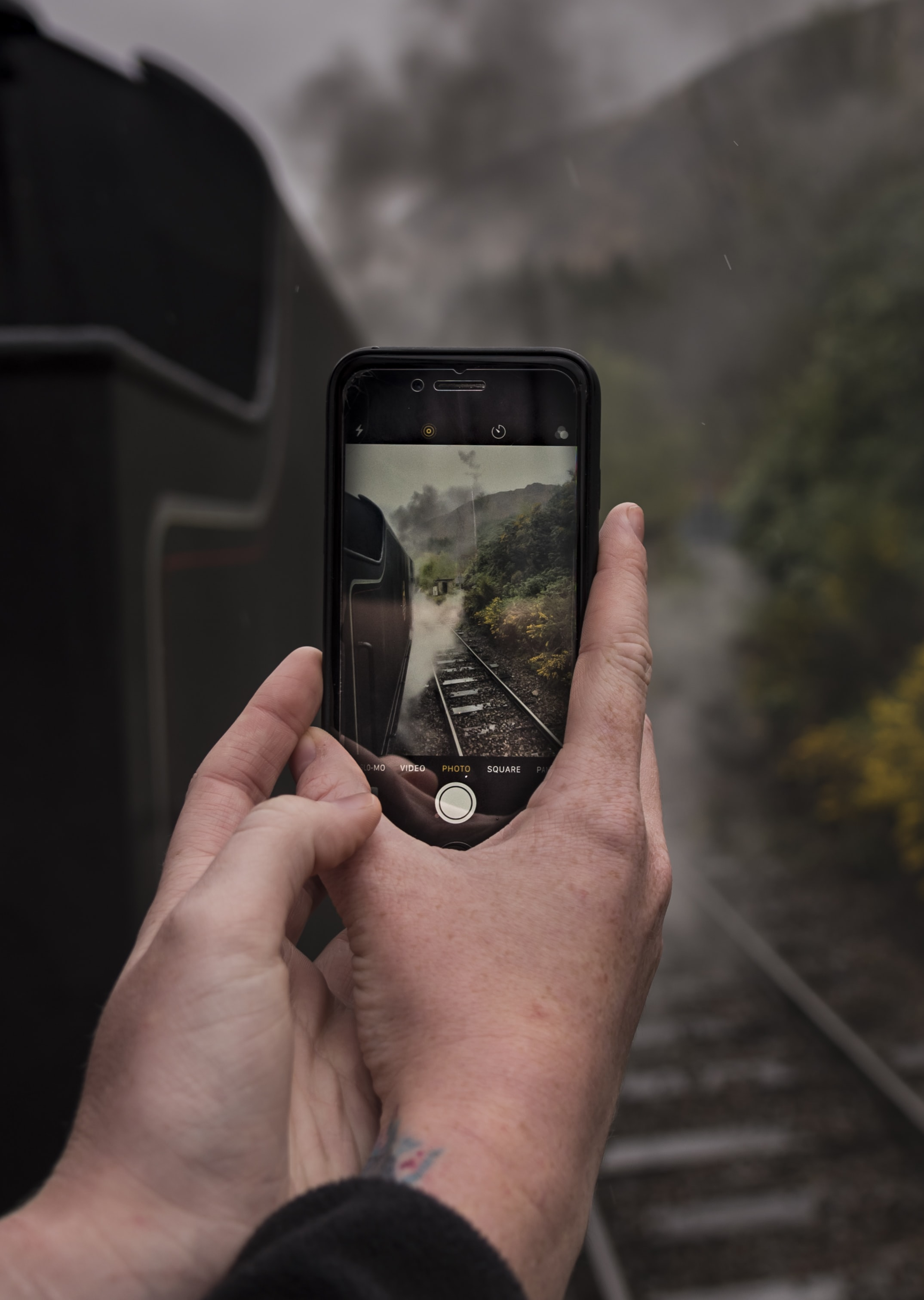 person taking photo of railway using iPhone