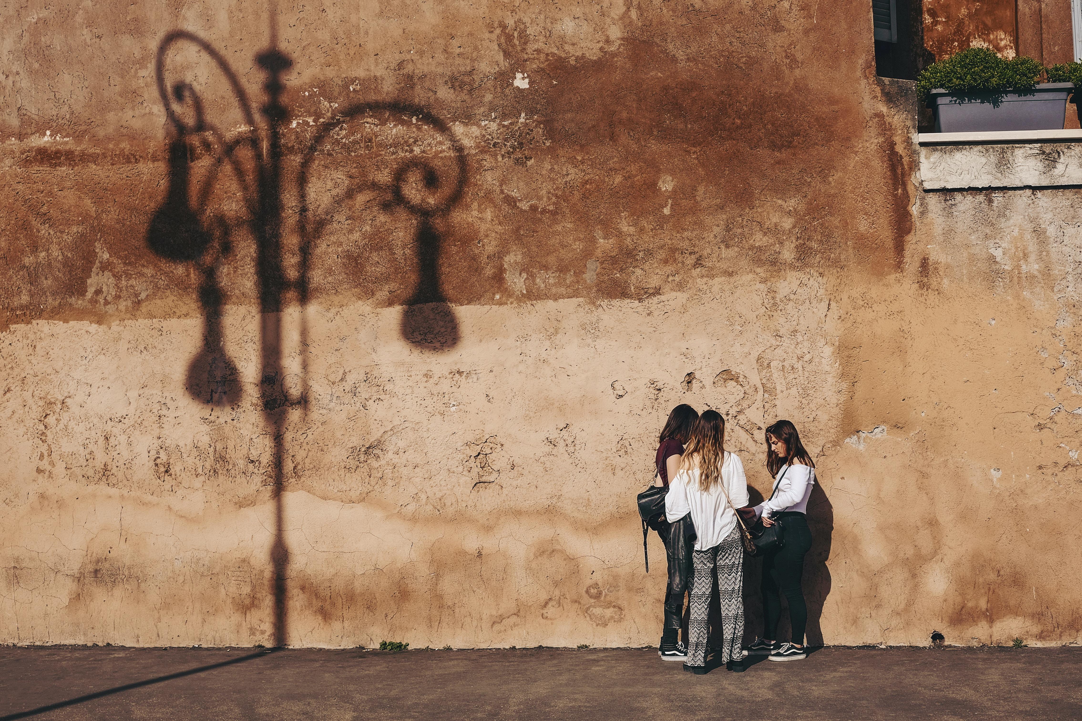 three women standing near brown wall